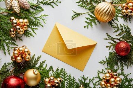 Photo pour Top vue de la brillante décoration de Noël dorée et rouge sur les branches vertes de thuja et enveloppe isolée sur blanc - image libre de droit
