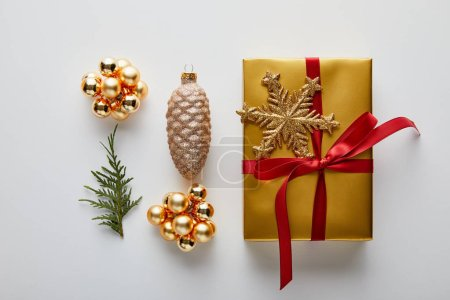 Photo for Flat lay with shiny golden Christmas decoration, gift and green thuja branch isolated on white - Royalty Free Image