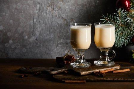 Photo pour Verres avec une délicieuse boisson aux oeufs sur une planche à découper près d'une branche d'épinette sur fond de pierre grise - image libre de droit