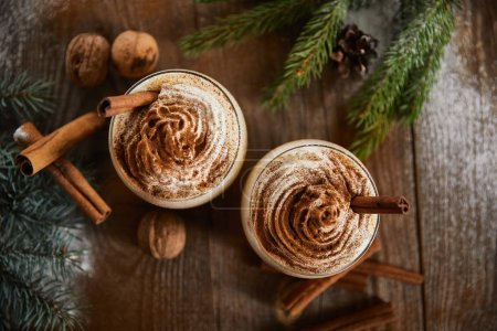 Photo pour Top view of delicious eggnog drink near spruce branches, wallnuts and cannon sticks on wooden table. - image libre de droit