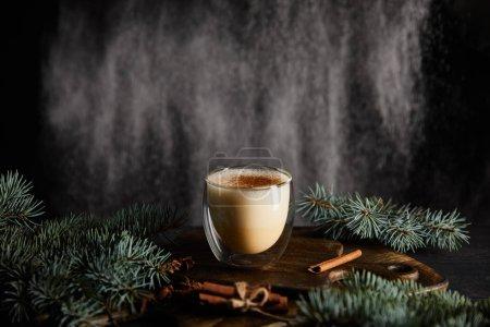 Photo pour Savoureux cocktail de lait de poule sur planche à découper près des branches d'épinette et des bâtons de cannelle sur fond noir avec du sucre en poudre tombant comme de la neige - image libre de droit