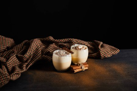 Photo for Delicious eggnog cocktail, cinnamon sticks and checkered cloth on table covered with cinnamon powder isolated on black - Royalty Free Image