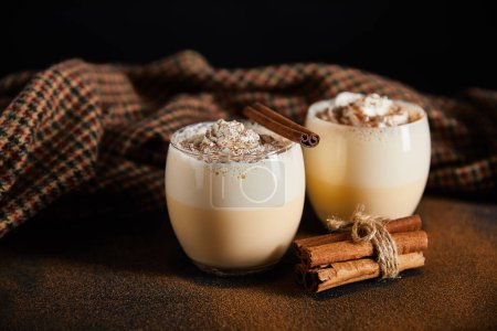 delicious eggnog cocktail, cinnamon branches and checkered cloth on table covered with cinnamon powder isolated on black