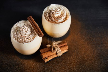 Photo for Delicious eggnog cocktail with whipped cream and cinnamon sticks on table covered with cinnamon powder - Royalty Free Image