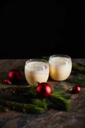 Photo pour Cocktail traditionnel de noix d'oeuf près d'une branche d'épinette et balles de Noël sur une surface de marbre foncé isolées sur fond noir - image libre de droit