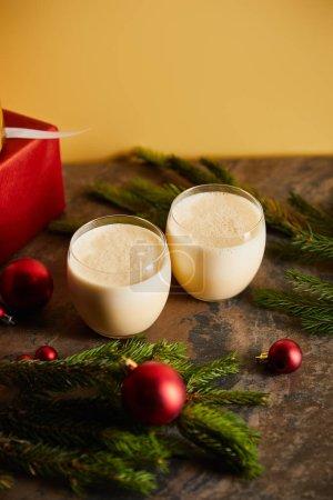 Photo pour Délicieux cocktail de noix d'oeuf, boîtes cadeaux, branches d'épinette et balles de Noël sur table de marbre foncé isolée sur orange - image libre de droit