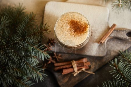 Foto de Vista superior del cóctel de eggnog aromatizado en el tablero de corte cubierto de polvo de azúcar, palillos de canela y ramas de abeja. - Imagen libre de derechos