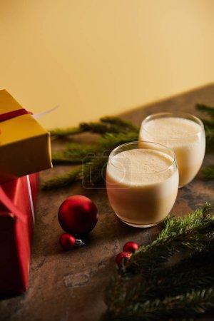 """Photo pour Cocktail traditionnel aux aubergines, boîtes cadeaux, branches d """"épinette et balles de Noël sur table en marbre foncé isolée sur orange - image libre de droit"""