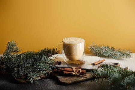 Photo pour Cocktail de lait de poule sur table recouvert de sucre en poudre, branches d'épinette et bâtonnets de cannelle isolés sur orange - image libre de droit