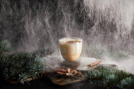 Photo pour Savoureux cocktail de eggnog sur planche à découper près des branches d'épinette et bâtonnets de cannelle sur fond noir avec du sucre en poudre tombant comme de la neige - image libre de droit
