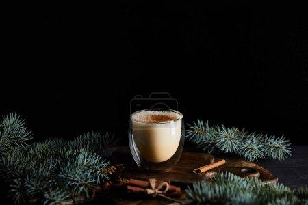 Photo pour Délicieux cocktail de noix d'oeuf sur une planche à découper près des branches d'épinette et cannelle isolés sur bâtonnets noirs - image libre de droit