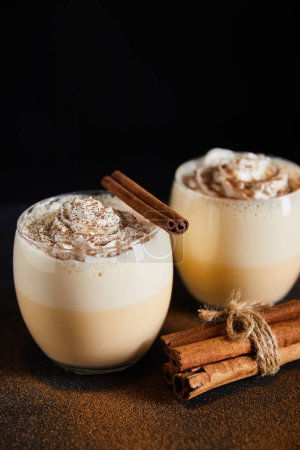 Photo pour Délicieux cocktail de noix d'oeuf avec crème fouettée et bâtonnets de cannelle sur table recouvert de poudre de cannelle isolée sur fond noir - image libre de droit