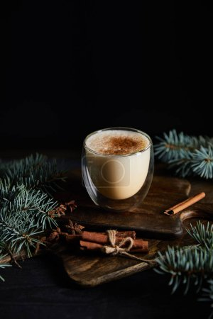 Photo pour Cocktail de noix d'oeuf aromatisé sur planche à découper, bâtonnets de cannelle et branches d'épinette isolés sur fond noir. - image libre de droit