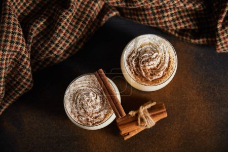 Photo for Top view of eggnog cocktail with whipped cream, cinnamon sticks and checkered cloth on table covered with cinnamon powder - Royalty Free Image