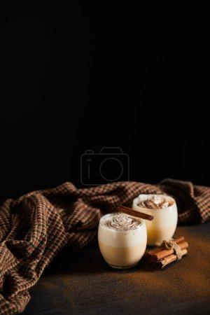 Photo pour Eggnog cocktail avec crème fouettée, bâtonnets de cannelle et tissu à carreaux sur table recouvert de poudre de cannelle isolée sur fond noir - image libre de droit