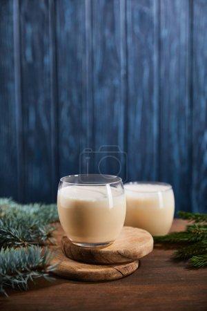 Photo pour Délicieux cocktail de noix d'oeuf sur planches rondes en bois près des branches d'épinette sur fond bleu texturé - image libre de droit