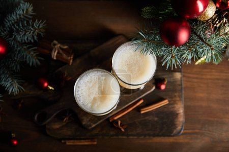 Photo pour Top view of eggnog cocktail, cutting board, cannelle sticks, spruce branches and Christmas balls on wooden table - image libre de droit
