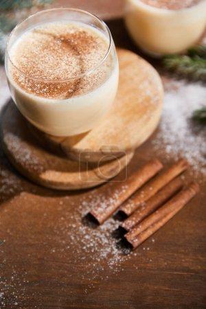 Photo pour Cocktail de noix d'oeuf aromatisé sur des planches rondes près des branches d'épinette et bâtonnets de cannelle sur une table en bois recouverte de sucre en poudre - image libre de droit