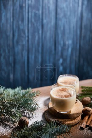 Photo pour Cocktail de noix d'oeuf aromatisé, branches d'épinette, bâtonnets de cannelle et noix sur table en bois recouverte de poudre de sucre sur fond bleu texturé - image libre de droit