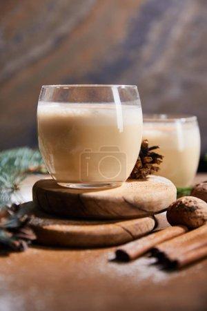 accent sélectif de délicieux cocktail au lait de poule sur des planches rondes, cônes d'épinette, bâtonnets de cannelle et noix sur fond de pierre de marbre