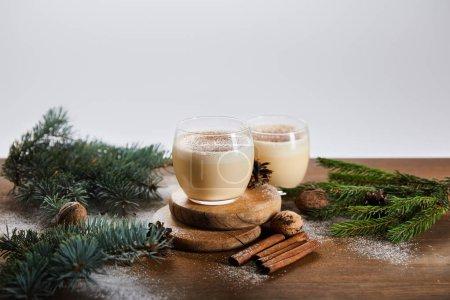Photo pour Cocktail de noix d'oeuf aromatisé sur planches rondes, branches d'épinette, bâtonnets de cannelle et noix isolés sur - image libre de droit