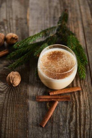 Photo pour Délicieux cocktail de noix d'oeuf près de la branche d'épinette, bâtonnets de cannelle et noix sur table en bois - image libre de droit