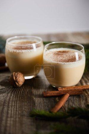 Photo pour Mise au point sélective d'un cocktail aromatisé au lait de poule près des bâtonnets de cannelle et des noix sur une table en bois isolée sur gris - image libre de droit