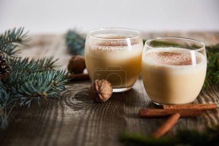 Photo pour Foyer sélectif de cocktail au lait de poule aromatisé près de bâtonnets de cannelle, noix et branches d'épinette sur table en bois isolé sur gris - image libre de droit