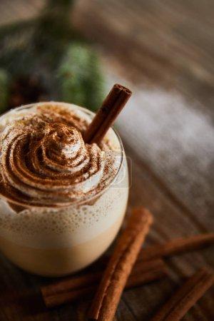 Photo pour Vue rapprochée de boisson au lait de poule aromatisée avec crème fouettée sur une table en bois près de bâtons de cannelle - image libre de droit