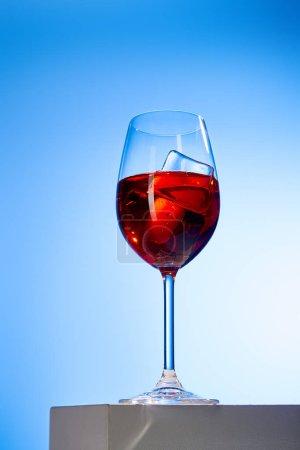 Foto de Cocktail Aperol Spritz con cubos de hielo en vidrio en fondo azul. - Imagen libre de derechos