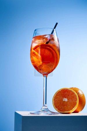 cocktail Aperol Spritz avec paille en verre et oranges sur fond bleu