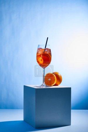Photo pour Cocktail Aperol Spritz avec paille en verre et oranges sur fond bleu - image libre de droit