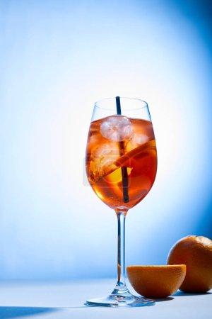 cóctel Aperol Spritz con paja en vidrio y naranjas sobre fondo azul