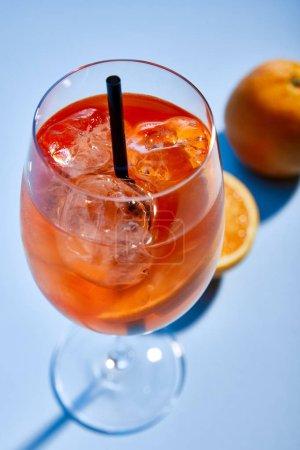 Foto de Enfoque selectivo del cóctel Aperol Spritz con paja en vidrio y naranjas en fondo azul. - Imagen libre de derechos