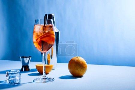 Photo pour Cocktail Aperol Spritz, oranges, agitateur, glaçons et tasse à mesurer sur fond bleu - image libre de droit