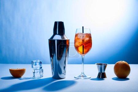 Photo pour Cocktail Aperol Spritz, oranges, shaker, glaçons et tasse à mesurer sur fond bleu - image libre de droit