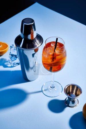 Foto de Vista panorámica del cóctel Aperol Spritz, naranja, batidora, cubos de hielo y taza de medición en fondo azul. - Imagen libre de derechos