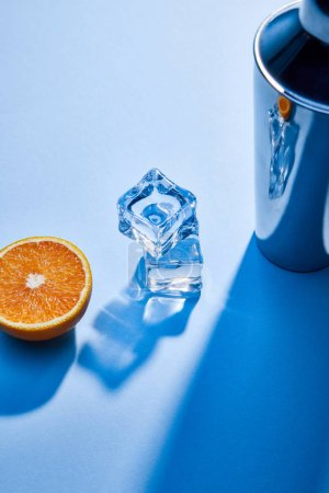 Photo pour Vue grand angle de l'orange, shaker, glaçons sur fond bleu - image libre de droit