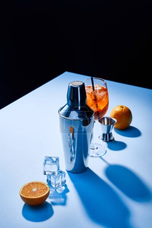 Photo for Cocktail Aperol Spritz, oranges, shaker, ice cubes and measuring cup on blue background - Royalty Free Image