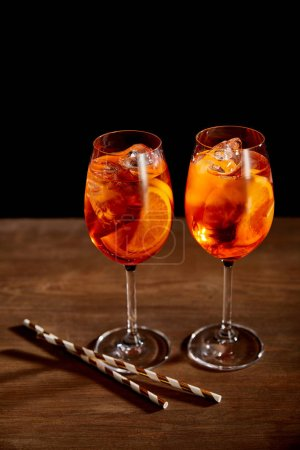 Aperol Spritz en vasos con paja sobre mesa de madera