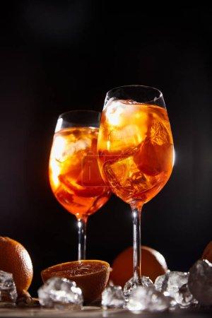 Aperol Spritz en verres, oranges et glaçons sur fond noir