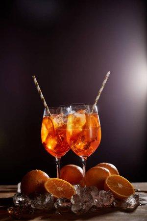 Aperol Spritz en vasos, naranjas y cubitos de hielo sobre fondo negro