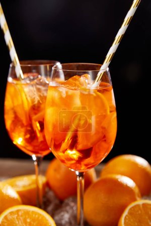 Aperol Spritz in glasses and oranges on black background