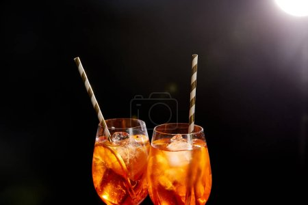Aperol Spritz in glasses with straws on black background