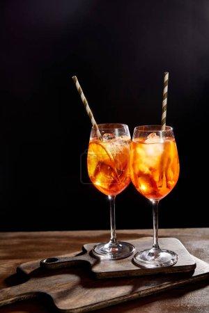 Photo pour Aperol Spritz dans des verres avec pailles sur des planches à découper - image libre de droit