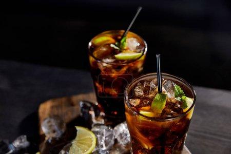 Foto de Cocktails cuba gratis en gafas con pajas, cubos de hielo y tapas en fondo negro. - Imagen libre de derechos