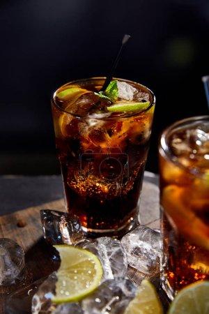 Foto de Enfoque selectivo de cócteles cuba libre en gafas con pajas, cubos de hielo y tapas sobre fondo negro. - Imagen libre de derechos