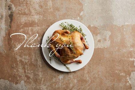 Photo pour Vue de dessus de dinde grillée entière avec romarin sur surface texturée de pierre avec illustration merci - image libre de droit