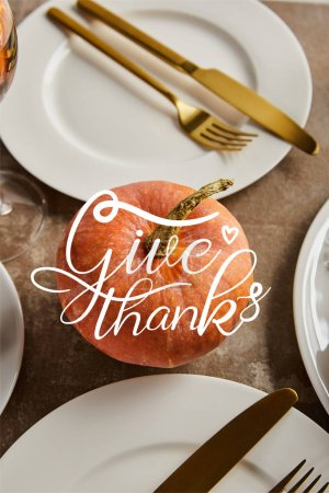whole ripe pumpkin with give thanks illustration near white plates with golden knives and forks on stone table