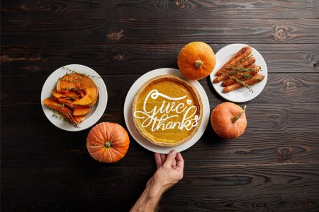 Photo for Partial view of male hand near plate with pumpkin pie and give thanks illustration, baked whole carrot, sliced and whole pumpkins on dark wooden table - Royalty Free Image